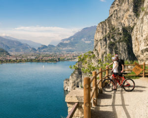 Garda, Italy - April 15, 2016: Two cyclists look the panorama from the Ponale trail in Riva del Garda, Italy.